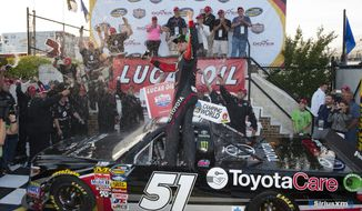 Kyle Busch celebrates his win in the NASCAR Truck Series auto race, Friday, May 30, 2014, at Dover International Speedway in Dover, Del. (AP Photo/Molly Riley)
