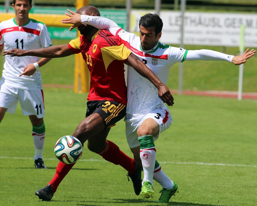 Iran's Ehsan Hajisafi, right, challenges for a ball with Jose  Vunguidica, left, of Angola during a friendly soccer match between Iran and Angola, in Hartberg, Austria, Friday, May 30, 2014. (AP Photo/Ronald Zak)