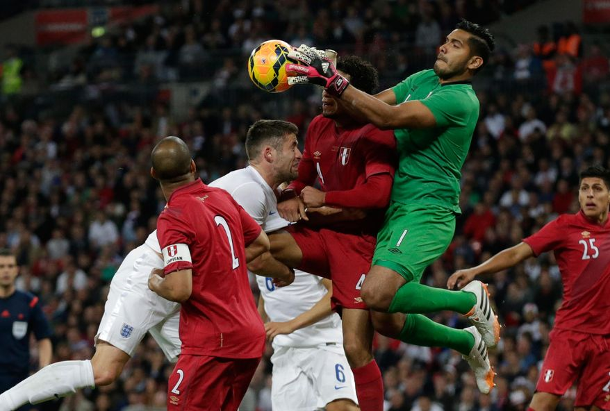 England's Gary Cahill, second left, competes for the ball with Peru's Alexander Callens, center, and goalkeeper Raul Fernandez, second right, during the international friendly soccer match between England and Peru at Wembley Stadium in London, Friday, May 30, 2014.  (AP Photo/Matt Dunham)