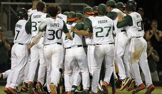 Miami players mob David Thompson after he scored the game-winning run against Bethune-Cookman during the ninth inning of an NCAA college baseball regional tournament game in Coral Gables, Fla., Friday, May 30, 2014. Miami won 1-0. (AP Photo/Alan Diaz)