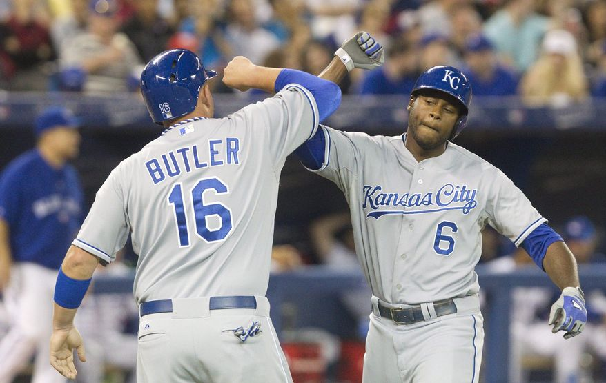 Kansas City Royals' Lorenzo Cain, right, is congratulated by Billy Butler at home plate after he drove Butler in with a two-run home run off Toronto Blue Jays starting pitcher J.A. Happ during the eighth inning of a baseball game in Toronto on Friday, May 30, 2014. (AP Photo/The Canadian Press, Fred Thornhill)