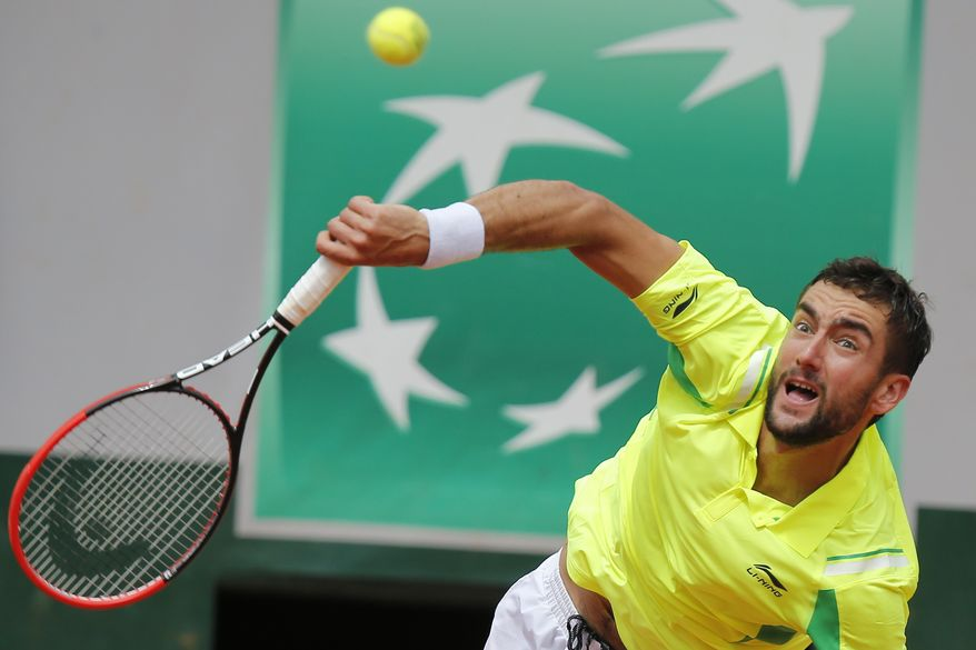 Croatia's Marin Cilic returns the ball during the third round match of the French Open tennis tournament against Serbia's Novak Djokovic at the Roland Garros stadium, in Paris, France, Friday, May 30, 2014.  (AP Photo/David Vincent)