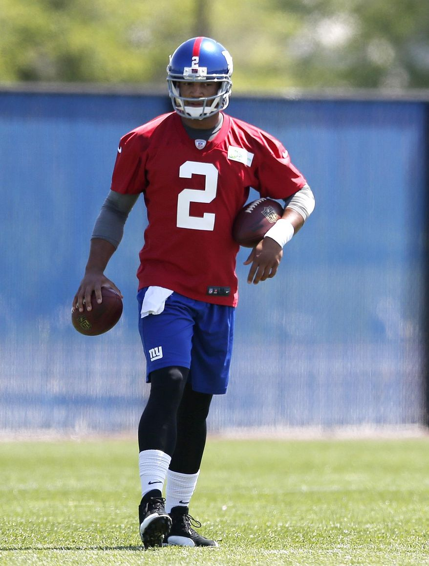 New York Giants quarterback Josh Freeman holds footballs during an NFL football organized team activity, Thursday, May 29, 2014, in East Rutherford, N.J. (AP Photo/Julio Cortez)