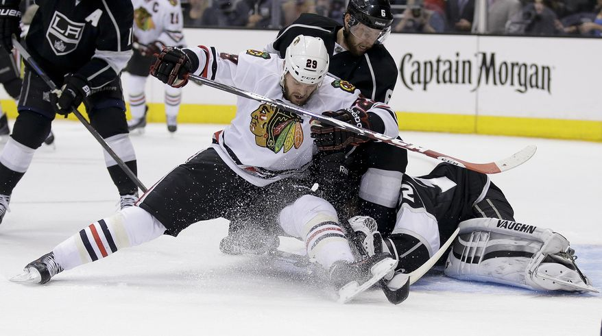 Los Angeles Kings goalie Jonathan Quick, right, blocks a shot by Chicago Blackhawks left wing Bryan Bickell as Kings' Jake Muzzin helps defend during first period of Game 6 of the Western Conference finals of the NHL hockey Stanley Cup playoffs, in Los Angeles on Friday, May 30, 2014. (AP Photo/Chris Carlson)