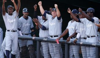 Jackson State's dugout celebrates after teammate Desmond Russell (not shown) scored the team's only run in the fourth inning during an NCAA college baseball tournament regional game against Louisiana-Lafayette in Lafayette, La., Friday, May 30, 2014. Jackson State won 1-0. (AP Photo/Jonathan Bachman)