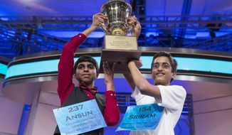 Ansun Sujoe, 13, of Fort Worth, Texas, left, and Sriram Hathwar, 14, of Painted Post, N.Y., raise the championship trophy after being named co-champions of the National Spelling Bee, on Thursday, May 29, 2014, in Oxon Hill, Md. (AP Photo/Evan Vucci)