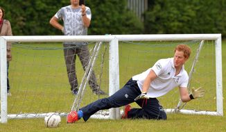 Britain's Prince Harry saves a penalty with his right foot, despite guarding two goals, during a short soccer kick about at the Inspire Suffolk centre for young people in Ipswich, eastern England, Thursday May 29, 2014. The prince began his day at the youth organisation which uses education and sport to improve young people's lives. (AP Photo/John Stillwell, Pool)