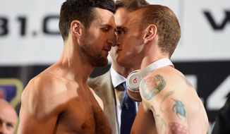 British boxers, Carl Froch, left and George Groves, go face to face, during the official weigh-in ahead of their super-middleweight world title rematch on Saturday, at Wembley Arena, in London, Friday May 30, 2014. Froch and Groves were given a taste of the atmosphere they can expect in their super-middleweight world title rematch when an estimated 7,000 raucous fans turned out just to watch their weigh-in on Friday. Both fighters made weight, with WBA and IBF champion Froch weighing 167 pounds, 9 ounces — just over a pound heavier than the challenger. (AP Photo/PA,  Adam Davy) UNITED KINGDOM OUT