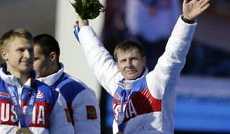 FILE - In this Sunday, Feb. 23, 2014 file photo, the team from Russia RUS-1, with Alexander Zubkov, right, Alexey Negodaylo, Dmitry Trunenkov, and Alexey Voevoda, wave to the crowd after they received the gold medal during the men's four-man bobsled competition final at the 2014 Winter Olympics, in Krasnaya Polyana, Russia. Olympic bobsled champion Alexander Zubkov was injured after unknown attackers smashed up the car he received for winning two gold medals at the Sochi Games. Zubkov was involved in a confrontation outside his Moscow home on Thursday, May 29, 2014, when attackers with bats smashed the lights and windshield of his Mercedes-Benz, one of the cars given by the Russian state to each of the country's gold medalists in Sochi. (AP Photo/Natacha Pisarenko, File)