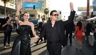 """FILE - In this Wednesday, May 28, 2014 file photo, Angelina Jolie, left, and Brad Pitt arrive at the world premiere of """"Maleficent"""" at the El Capitan Theatre in Los Angeles. A man who accosted Pitt on a red carpet has pleaded no contest to battery and been ordered to stay away from the actor and Hollywood red carpet events. Vitalii Sediuk entered the plea during a Los Angeles court appearance Friday, May 30, 2014, two days after he leaped from a fan area and made contact with Pitt at the """"Maleficent"""" premiere. (Photo by John Shearer/Invision/AP, file)"""