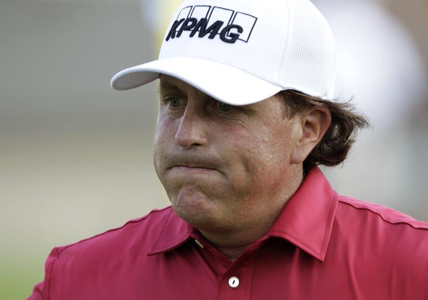 Phil Mickelson reacts after making double bogey on the 17th hole during the first round of the Memorial golf tournament Thursday, May 29, 2014, in Dublin, Ohio. (AP Photo/Jay LaPrete)
