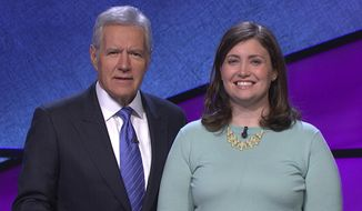 """FILE - This January 2014 file photo provided by Jeopardy Productions, Inc., shows Alex Trebek, left, host of the TV show """"Jeopardy!,"""" poses with contestant Julia Collins, 31, of Kenilworth, Ill., during the taping of her shows on stage at """"Jeopardy!"""", Sony Pictures Studios, Culver City, Calif.  Collins can count another """"Jeopardy!"""" victory and another milestone. She won her 20th game Friday, May 30, 2014, putting her alone in second place for most consecutive non-tournament victories on the TV game show.  (AP Photo/Courtesy of Jeopardy Productions, Inc., file)"""