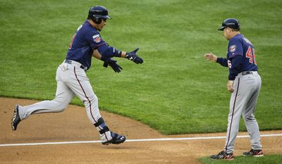 Minnesota Twins' Oswaldo Arcia, left, is greeted by Twins third base coach Joe Vavra (46) while rounding the bases after hitting a solo home run during the second inning against the New York Yankees, Friday, May 30, 2014, in New York. (AP Photo/Julie Jacobson)