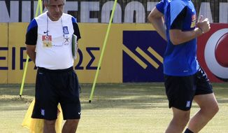 Greece's coach Fernando Santos, left, of Portugal watches his players during a training session in Athens on Thursday, May 29, 2014. Greece trained for the last time in Athens before its departure on Friday abroad for preparations ahead the World Cup. The Greeks face Portugal Saturday in the first of three warm-up matches, and will arrive at the sports camp in Aracaju, Brazil on Saturday, June 7. Greece will play in Group C, against Colombia, Japan and Ivory Coast at the World Cup in Brazil. (AP Photo/Thanassis Stavrakis)