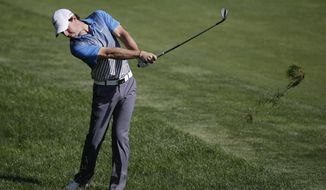Rory McIlroy, of Northern Ireland, hits from the rough on the 14th hole during the second round of the Memorial golf tournament Friday, May 30, 2014, in Dublin, Ohio. (AP Photo/Darron Cummings)
