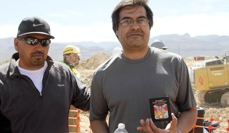 FILE - In this April 26, 2014 file photo,left, and Raul Ruiz pose for a photograph with a cartridge they found buried in a landfill in Alamogordo, N.M. Producers of a documentary dug in an southeastern New Mexico landfill in search of millions of cartridges of the Atari 'E.T. the Extra-Terrestrial' game that has been called the worst game in the history of video gaming and were buried there in 1983.  Officials in  Alamogordo, are working on a plan under which film companies, museums and the public could get Atari video games that were dug up from the old landfill last month. (AP Photo/Juan Carlos Llorca)