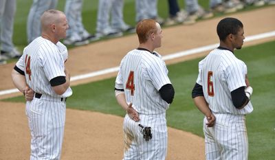 Maryland head coach John Szfec (14), Charlie White (4) and LaMonte Wade Jr. (6) stand during the national anthem before an NCAA college baseball regional tournament game against Old Dominion in Columbia, S.C., Friday, May 30, 2014. (AP Photo/Richard Shiro)