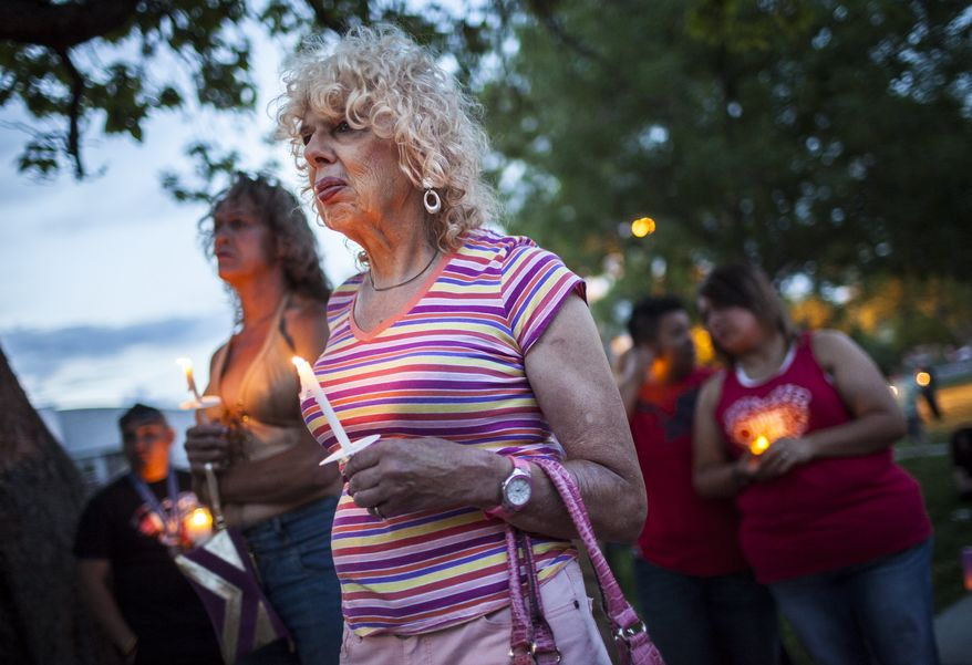 In this May 29, 2014 photo, Denee Mallon, center, joins a candlelight vigil organized by Albuquerque Pride in Albuquerque, N.M. A U.S. Department of Health and Services review board ruled Friday, May 30, in favor of Mallon, a 74-year-old Army veteran, whose request to have Medicare pay for her genital reconstruction was denied two years ago. The decision recognizes sex reassignment surgeries as a medically necessary and effective treatment for individuals who do not identify with their biological sex. (AP Photo/Craig Fritz)