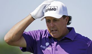 Phil Mickelson adjust his hat as he walks off the first tee during the third round of the Memorial golf tournament Saturday, May 31, 2014, in Dublin, Ohio.  Mickelson says he's co-operating in an insider trading investigation involving him, investor Carl Icahn and Las Vegas gambler Billy Walters but maintains he did nothing wrong. Mickelson's manager confirmed Saturday that the investigation was the same outlined in reports in several newspapers, including the Wall Street Journal. (AP Photo/Darron Cummings)