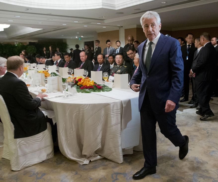 U.S. Defense Secretary Chuck Hagel walks to his seat as he arrives for the official luncheon at the 13th Asia Security Summit, Saturday, May 31, 2014 in Singapore. (AP Photo/Pablo Martinez Monsivais, Pool)