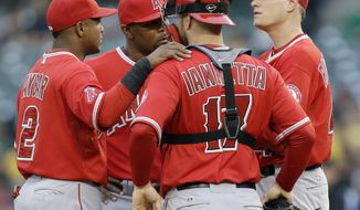Los Angeles Angels starting pitcher Garrett Richards, right, talks with teammates Chris Iannetta (17), Howie Kendrick, second from left, and Erick Aybar (2) on the mound after walking the bases loaded against the Oakland Athletics during the first inning of a baseball game Friday, May 30, 2014, in Oakland, Calif. (AP Photo/Marcio Jose Sanchez)