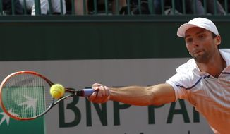 Croatia's Ivo Karlovic returns the ball to South Africa's Kevin Anderson during their third round match of  the French Open tennis tournament at the Roland Garros stadium, in Paris, France, Saturday, May 31, 2014. (AP Photo/Michel Euler)