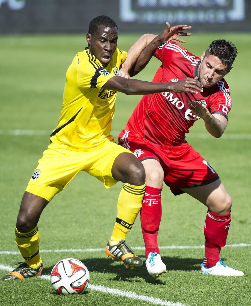Toronto FC midefielder Brad Orr, right, vies for the ball against Columbus Crew midfielder Tony Tchani during the first half of an MLS soccer game in Toronto on Saturday, May 31, 2014. (AP Photo/The Canadian Press, Nathan Denette)