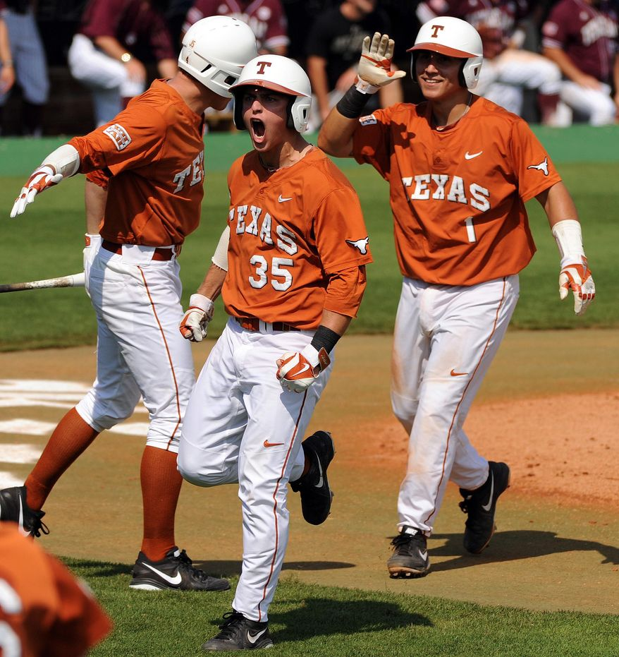 Texas' Madison Carter, center, celebrates after scoring during the third inning against Texas A&M in an NCAA college baseball tournament regional game Friday, May 30, 2014, at Reckling Park in Houston. (AP Photo/Houston Chronicle, Eric Christian Smith) MANDATORY CREDIT