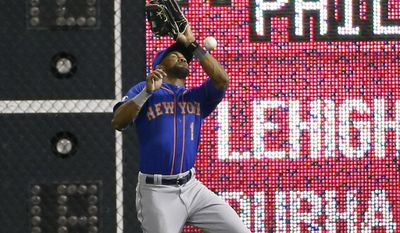 New York Mets right fielder Chris Young cannot catch a hit by Philadelphia Phillies' Marlon Byrd during the 14th inning of a baseball game, Saturday, May 31, 2014, in Philadelphia. Byrd reached first base on the fielding error by Young. Philadelphia won 6-5 in 14 innings. (AP Photo/Matt Slocum)