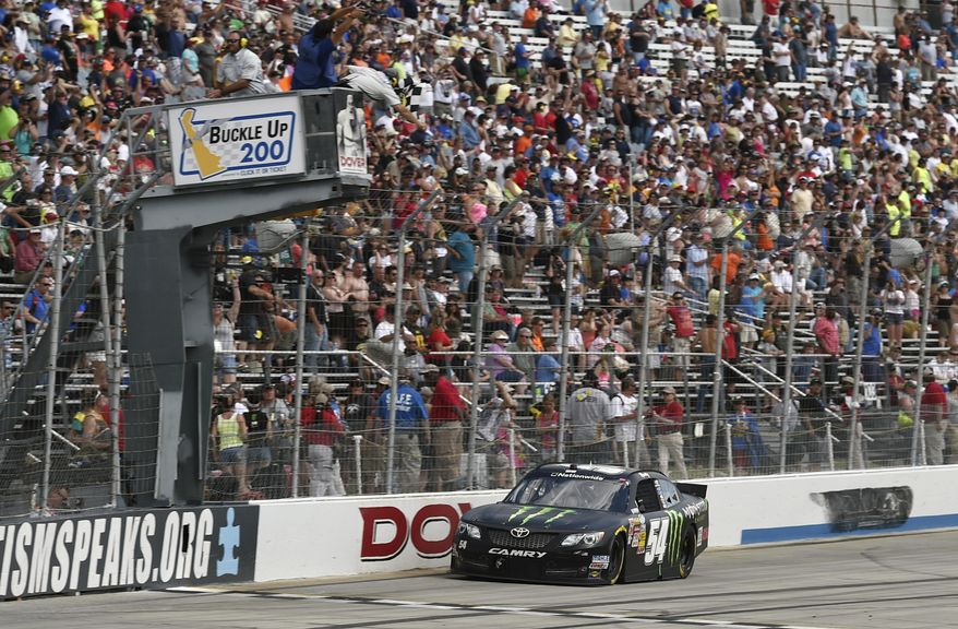 Kyle Busch takes the checkered flag to win the NASCAR Nationwide series auto race, Saturday, May 31, 2014, at Dover International Speedway in Dover, Del. (AP Photo/Molly Riley)