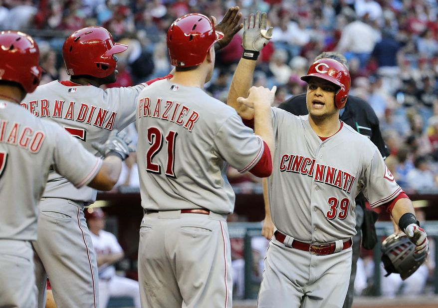 Cincinnati Reds' Devin Mesoraco (39) is congratulated by teammates Todd Frazier (21), Ramon Santiago, left, and Roger Bernadina after hitting a grand slam against the Arizona Diamondbacks during the second inning of a baseball game, Friday, May 30, 2014, in Phoenix. (AP Photo/Matt York)