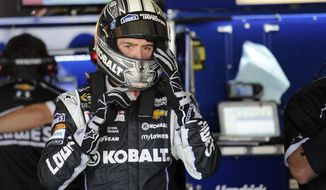 Jimmie Johnson adjusts his helmet during practice for the NASCAR Sprint Cup series auto race, Saturday, May 31, 2014, at Dover International Speedway in Dover, Del. (AP Photo/Nick Wass)