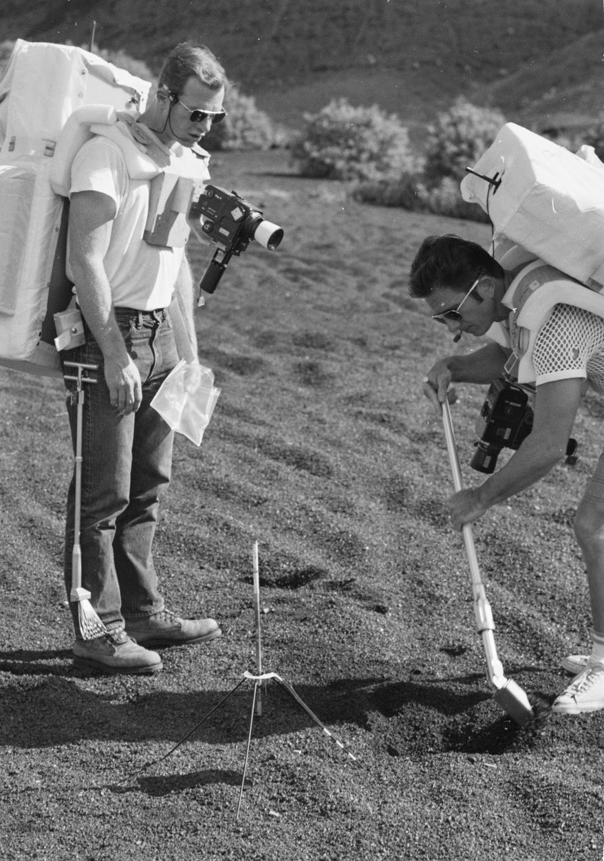 """This Dec. 1970 image provided by NASA shows Apollo 15 commander,Dave Scott and lunar module pilot Jim Irwin training on the Big Island, Hawaii. Before many Apollo astronauts went to the moon, they came to Hawaii to train on the Big Island's lunar landscapes. Now, decades-old photos are surfacing of astronauts scooping up Hawaii's soil and riding across volcanic fields in a """"moon buggy"""" vehicle.(AP Photo/NASA)"""