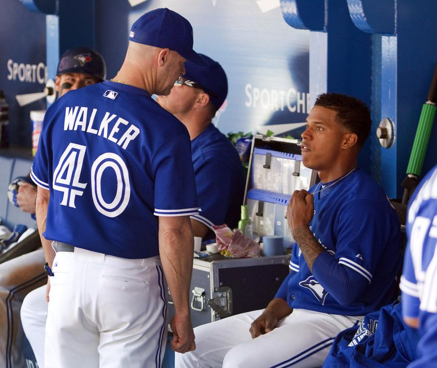 Toronto Blue Jays pitching coach Pete Walker talks to starting pitcher Marcus Stroman after he came out of the game at the end of the seventh inning of a baseball game against the Kansas City Royals  in Toronto, Saturday, May 31, 2014. (AP Photo/The Canadian Press, Fred Thornhill)