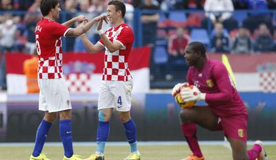 Croatia'sIvan Perisic, center, celebrates his second goal with Vedran Corluka during the internationa friendly soccer match between Croatia and Mali, in Osijek, Croatia, Saturday, May 31, 2014. (AP Photo/Darko Bandic)