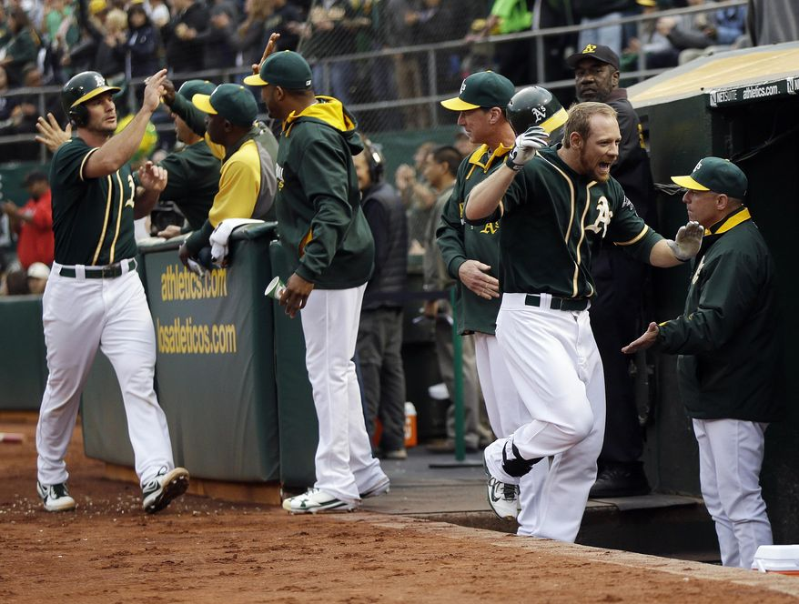 Oakland Athletics' Brandon Moss, right, celebrates with teammates in the dugout after his a grand slam against the Los Angeles Angels during the first inning of a baseball game Friday, May 30, 2014, in Oakland, Calif. (AP Photo/Marcio Jose Sanchez)