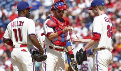 Philadelphia Phillies starting pitcher Kyle Kendrick, right, gets the ball back from catcher Wil Nieves, center, after giving up the second run to the New York Mets during the first inning of a baseball game, Saturday, May 31, 2014, in Philadelphia. (AP Photo/Chris Szagola)