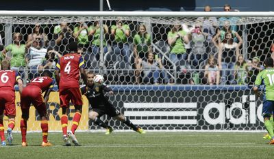 Seattle Sounders' Gonzalo Pineda, right, kicks a penalty kick that got past Real Salt Lake goalkeeper Jeff Attinella for a goal as RSL's Nat Borchers (6), Olmes Garcia (13), and Aaron Maund (4) look on during the first half of an MLS soccer match, Saturday, May 31, 2014, in Seattle. (AP Photo/Ted S. Warren)