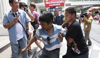A man, center, is detained by plainclothes police officers after holding an anti-coup sign outside a McDonald's restaurant in downtown Bangkok, Thailand Saturday, May 31, 2014. In his first address to the public since taking control of Thailand in a bloodless coup, army commander Gen. Prayuth Chan-ocha, the head of the military junta, said it could take more than a year for new elections to be held because peace and reforms must be achieved first. (AP Photo/Wason Wanichakorn)