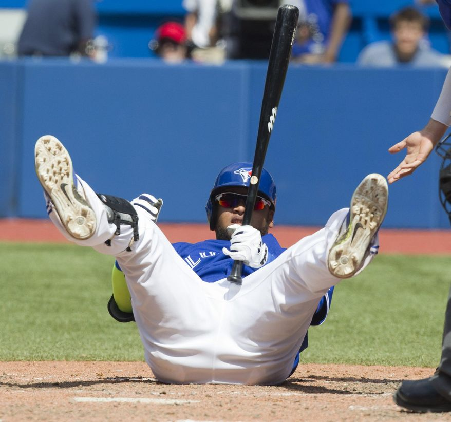 Toronto Blue Jays Juan Francisco lands on the ground after being hit by a pitch from Kansas City Royals Tim Collins during the seventh inning of a baseball game in Toronto, Saturday, May 31, 2014. (AP Photo/The Canadian Press, Fred Thornhill)