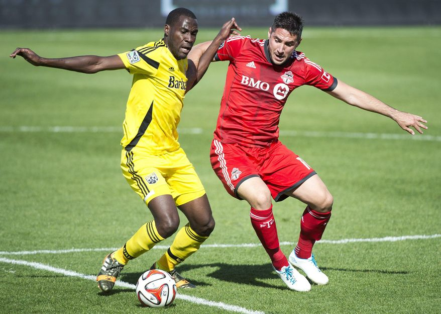 Toronto FC midefielder Brad Orr, right, competes for the ball against Columbus Crew midfielder Tony Tchani during the first half of an MLS soccer game in Toronto on Saturday, May 31, 2014. (AP Photo/The Canadian Press, Nathan Denette)