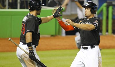 Miami Marlins' Giancarlo Stanton, right, celebrates with teammate Garrett Jones after scoring on a hit by teammate Casey McGehee in the eight inning of play against the Atlanta Braves during a baseball game in Miami, Saturday, May 31, 2014. (AP Photo/Joe Skipper)