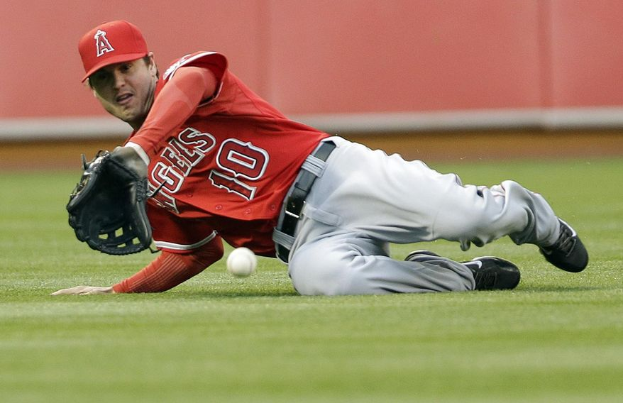 Los Angeles Angels left fielder Grant Green slides but can't catch a line drive from Oakland Athletics' Jed Lowrie during the first inning of a baseball game Friday, May 30, 2014, in Oakland, Calif. (AP Photo/Marcio Jose Sanchez)