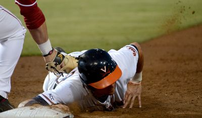 Virginia's Brandon Downes dives back to first base in time safely under the tag of Arkansas' Eric Fisher during the second inning of an NCAA college baseball regional tournament game in Charlottesville, Va., Saturday, May 31, 2014. (AP Photo/Pat Jarrett)