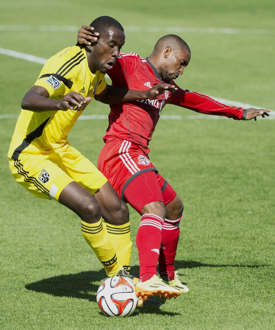 Toronto FC forward Jermain Defoe, right, battles for the ball against Columbus Crew midfielder Tony Tchani, left, during first half MLS soccer action in Toronto on Saturday May 31, 2014. (AP Photo/The Canadian Press, Nathan Denette)