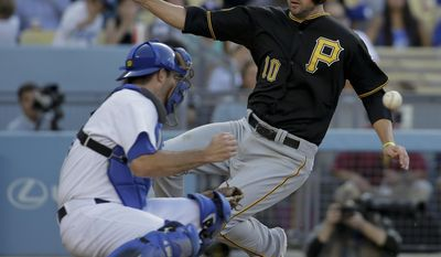 Pittsburgh Pirates' Jordy Mercer, right, scores past Los Angeles Dodgers catcher Drew Butera on a single by Travis Snider during sixth inning of a baseball in Los Angeles, Saturday, May 31, 2014. (AP Photo/Chris Carlson)