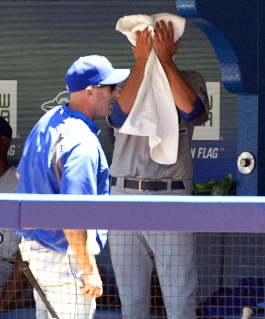 Kansas City Royals starting pitcher Aaron Brooks wipes his face in the dugout after being taken out after he gave up 7 runs to the Toronto Blue Jays in first inning of a baseball game in Toronto, Saturday, May 31, 2014. (AP Photo/The Canadian Press, Fred Thornhill)