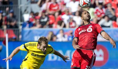 Toronto FC forward Luke Moore, right, heads the ball past Columbus Crew defender Tyson Wahl during the first half of an MLS soccer game in Toronto on Saturday, May 31, 2014. (AP Photo/The Canadian Press, Nathan Denette)