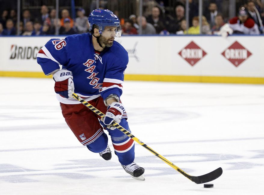 FILE - In this May 22, 2014, file photo, New York Rangers right wing Martin St. Louis (26) skates with the puck during the second period of Game 3 of the NHL hockey Stanley Cup playoffs Eastern Conference finals in New York. St. Louis and Dominic Moore have dealt with mourning and heartbreak during the New York Rangers' run to the Stanley Cup finals. Tragedy kept St. Louis away from hockey for just a day after the unexpected death of his mother. A rare illness that took the life of Moore's wife kept him out of the NHL for a year and a half. (AP Photo/Kathy Willens, File)