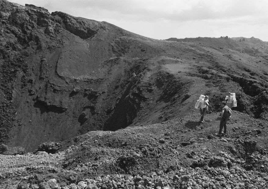 """This Dec. 1970 image provided by NASA shows Apollo 15 astronauts training on the Big Island of Hawaii. Before many Apollo astronauts went to the moon, they came to Hawaii to train on the Big Island's lunar landscapes. Now, decades-old photos are surfacing of astronauts scooping up Hawaii's soil and riding across volcanic fields in a """"moon buggy"""" vehicle. (AP Photo/NASA)"""
